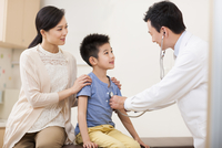 Doctor examining little boy with stethoscope
