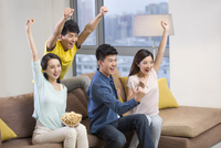 Cheerful young adults watching sports games on TV