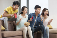 Young adults watching sports games on TV