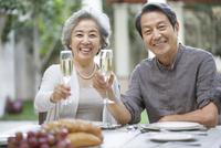 Senior couple celebrating with champagne 11091008025| 写真素材・ストックフォト・画像・イラスト素材|アマナイメージズ