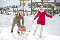 Young couple carrying Christmas Presents with sled