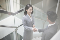 Business person shaking hands on the stairs