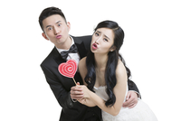 Happy bride and groom holding a heart-shaped lollipop