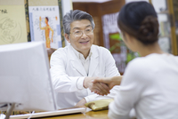 Senior Chinese doctor shaking hands with patient