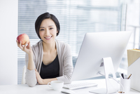 Young woman holding an apple in office