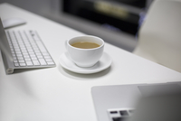 A cup of coffee and a laptop in office