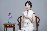 Young beautiful woman in traditional cheongsam eating porridge
