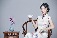 Young beautiful woman in traditional cheongsam eating porridge 11091018910| 写真素材・ストックフォト・画像・イラスト素材|アマナイメージズ