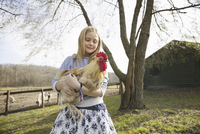 A girl holding a large chicken in an animal enclosure