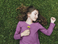 A ten year old girl lying, holding a dandelion flower.