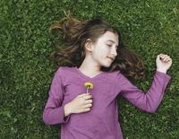 A ten year old girl lying, holding a dandelion flower.  11093001008| 写真素材・ストックフォト・画像・イラスト素材|アマナイメージズ