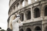 A woman outside the Colosseum amphitheatre in Rome 11093001176| 写真素材・ストックフォト・画像・イラスト素材|アマナイメージズ