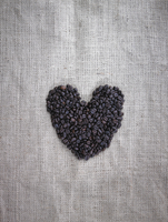Organic roasted coffee beans in a heart shape on a sack.
