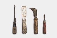 Used tools arranged in a row. Metal rusty and marked implements.
