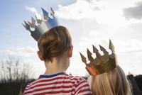 Two children in fancy dress, wearing crowns.