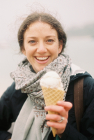 A woman holding out an icecream in a cone and laughing.