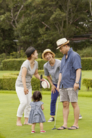 Family on a golf course.A child and three adults.
