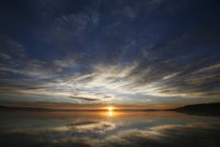 The sun on the horizon, seen over the waters of a lake. Dawn.