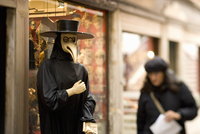 A person in a bird mask, a traditional carnival costume, with a long bird beak. A woman walking by.