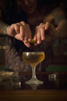A woman's hands squeezing a slice of lemon over a cocktail glass.
