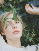 A blond haired woman looking wistfully through a vine with green leaves. 11093005340| 写真素材・ストックフォト・画像・イラスト素材|アマナイメージズ