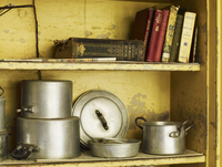 Old well worn recipe books and pots and pans on a kitchen shelf.
