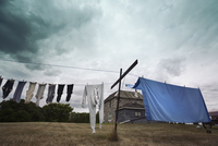 A washing line with clothes and sheets hanging out to dry under a stormy sky.