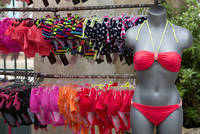 A clothes stall in the market, and a rack of women's swimwear. A pink bikini on a mannequin.