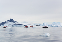 View of groups of people in rubber boats near and iceberg in the Antarctic.