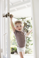 Young boy wearing T-Shirt and pants opening a door.