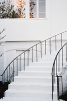 A historic late 18th century house with white walls and a curved exterior staircase