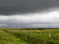 Dark rain clouds over farmland.