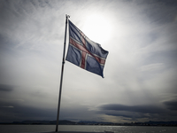 The national flag of Iceland, flying against a cloudy sky