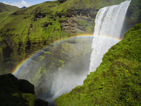 Skogafoss waterfall, a cascade over a sheer cliff, and a rainbow in the mist.