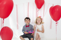 Young boy and girl posing for a picture in a photographers studio, surrounded by red balloons.