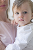 Close up of a young girl in her mother's arms.