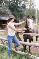 Woman feeding a horse in a paddock on a ranch.