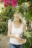 Blond woman in a garden, holding a plant pot.
