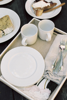 High angle view of a tray with mugs, plates and cutlery, pastries.