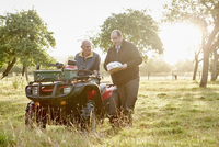Two men, a farmer and a man with a clipboard, by a quadbike in an orchard.