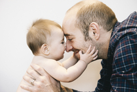 A young baby girl and her father face to face playing.