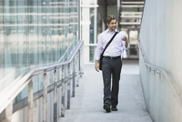 A man carrying a computer bag with a strap across his chest on along a city walkway.