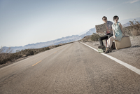 A young couple, man and woman, on a tarmac road in the desert hitchiking, with a sign saying Vegas or Bust.