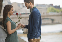 A couple in a romantic setting by a river. A man offering a woman a red rose.