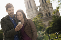 Two people, a couple standing close together taking a selfy outside the historic Notre Dame cathedral in Paris.