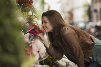A woman bending to smell the scent of flowers at a stall on the street.