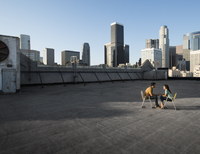 A couple, man and woman sitting in deck chairs on a rooftop overlooking city skyscrapers.  11093007898| 写真素材・ストックフォト・画像・イラスト素材|アマナイメージズ