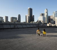 A couple, man and woman sitting in deck chairs on a rooftop overlooking city skyscrapers.
