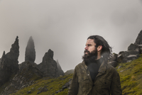 A man standing with a backdrop of rock pinnacles on the skyline, a dramatic windswept landscape and low cloud.