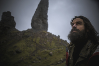 A man standing with a backdrop of rock pinnacles on the skyline towering over him, an overcast sky with low cloud.